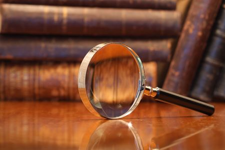 Still life with magnifying glass standing on wooden table on background with old books