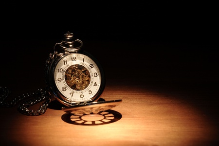 Stylish pocket watch on wooden surface under beam of light