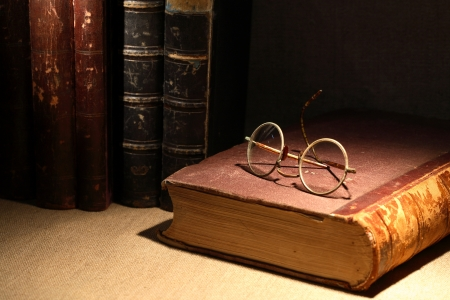 Vintage still life with old books and spectacles on canvas surface