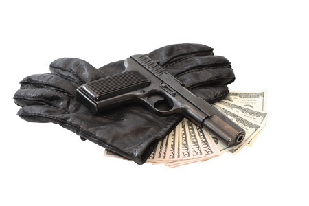 Gang concept. Pistol on black leather gloves and cash. Isolated with clipping path