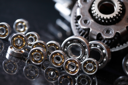 Machinery concept. Set of various gears and ball bearings on dark background