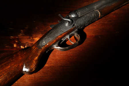 Foto de Ancient hunting shotgun closeup on wooden background - Imagen libre de derechos