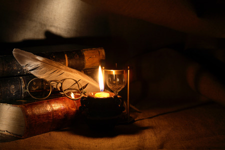 Photo pour Vintage still life with old glasses against lighting candle and books - image libre de droit