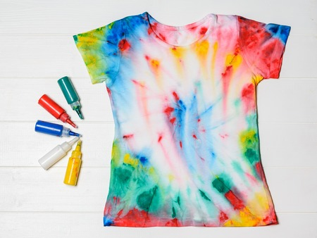 Photo for Tubes of paint for clothes and t-shirt in tie dye style on a white wooden table. White clothes painted by hand. Flat lay. - Royalty Free Image