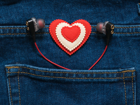 Photo pour Red and white heart with headphones sticking out of the pocket of jeans. Romantic style in fashionable clothes. - image libre de droit