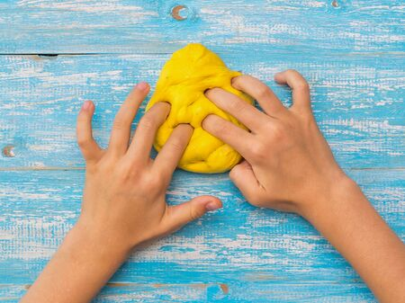Photo pour Girl kneads yellow slime on a blue wooden table. Toy antistress. Toy for the development of hand motor skills. - image libre de droit