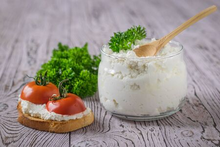 Photo pour A jar and bread with cottage cheese and tomatoes on a pink wooden table. The concept of a healthy diet. - image libre de droit