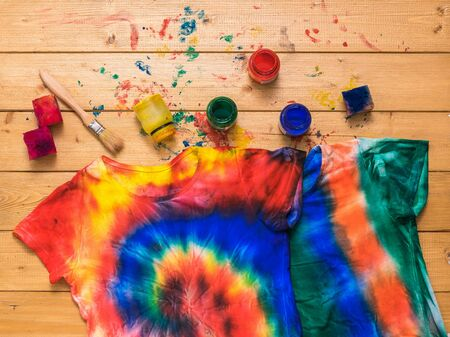 Photo pour The process of painting a t-shirt in the style of tie dye in the form of a spiral. White clothes painted by hand. Flat lay. - image libre de droit