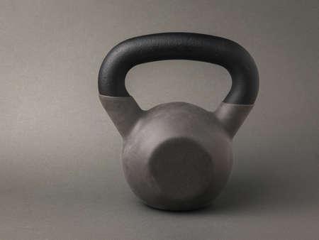 Foto de A gray sports kettlebell on a dark gray background. Sports lifestyle. - Imagen libre de derechos