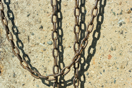 Chain hanging on a concrete wall background.