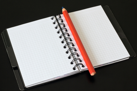 Notebook and red pencil on a black background.