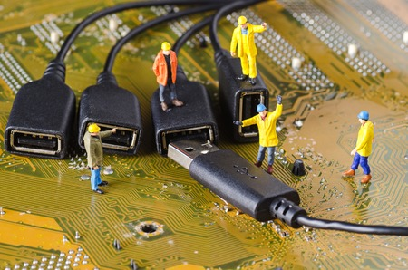 Miniature Technicians try to connecting data cable