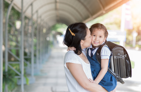 Foto de Mother kissing schoolgirl in uniform before going to school, Love and care concept. - Imagen libre de derechos