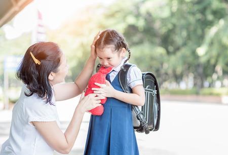 Foto de Mother standing at school holding hands and teaching her daughter, love concept . - Imagen libre de derechos