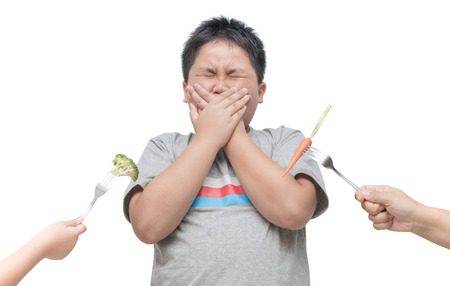 obese fat boy with expression of disgust against vegetables isolated on white background, Refusing food concept.