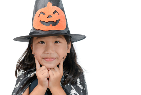 funny child girl in witch costume for Halloween with pumpkin Jack isolated on white background.