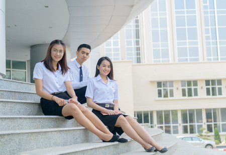 Foto de Happy asian students in uniform siting at university, education concept.. - Imagen libre de derechos