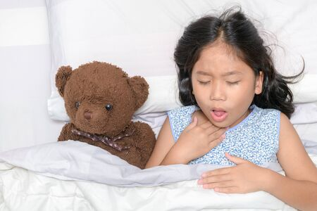 Photo for Little girl is coughing and sore throat lying on bed with toy bear, Health care concept.. - Royalty Free Image