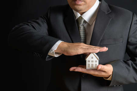 Photo pour Paper house is covered by business man hands of a real estate agent to protect the house for customers, homebuyers, insurance, ready give to with new owner. Home insurance sales concept. - image libre de droit