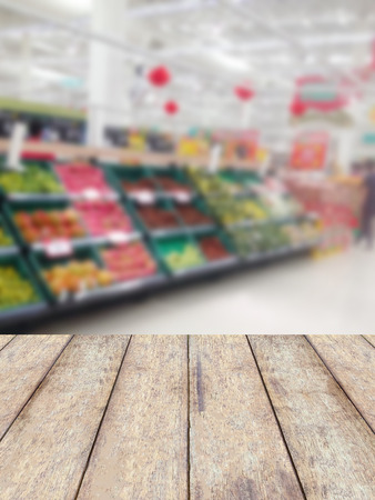wood counter product display with fruits shelves in supermarket blurred background