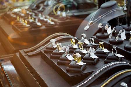 Gold jewelry diamond shop with rings and necklaces luxury retail store window display showcase