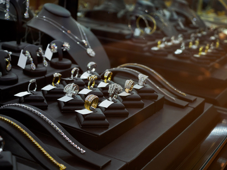 Photo pour Gold jewelry diamond shop with rings and necklaces luxury retail store window display showcase - image libre de droit