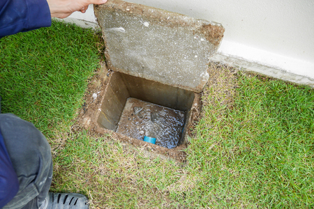 Photo pour Worker hand open sewer cover of new house - image libre de droit