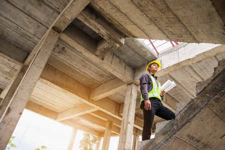 Foto de young professional engineer worker in protective helmet and blueprints paper on hand at the house building construction site - Imagen libre de derechos