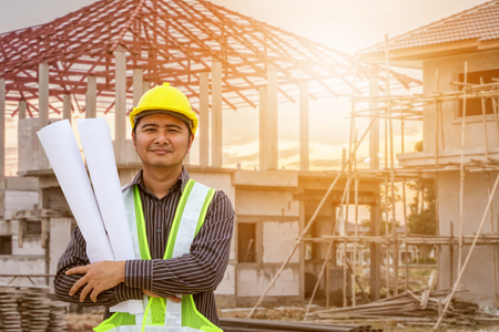 Photo pour Asian business man construction engineer worker in protective helmet and blueprints paper on hand at house building site - image libre de droit