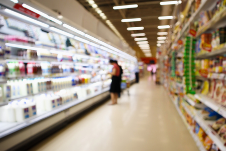Supermarket Aisle and Shelves with dairy products in refrigerator blur background