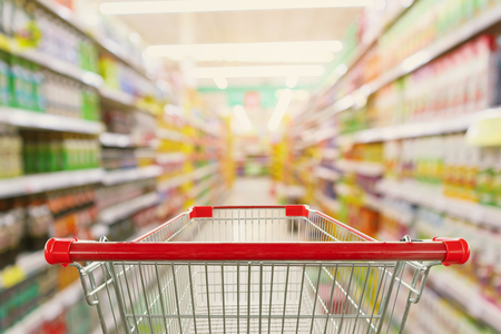 Foto de Supermarket aisle interior blur background with empty red shopping cart - Imagen libre de derechos