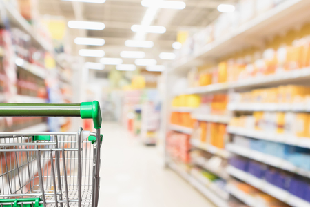 Empty green supermarket shopping cart with abstract blur grocery store aisle defocused background