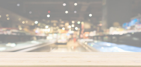 Empty wood table top with abstract supermarket aisle interior blurred defocused background with bokeh light