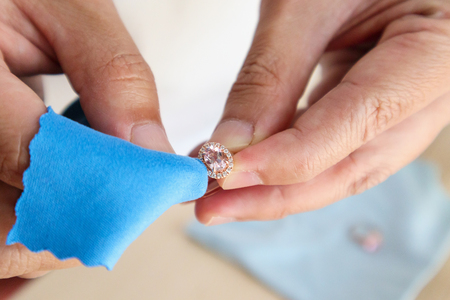 Photo for Jeweller hand polishing and cleaning jewelry diamond ring with micro fiber fabric - Royalty Free Image