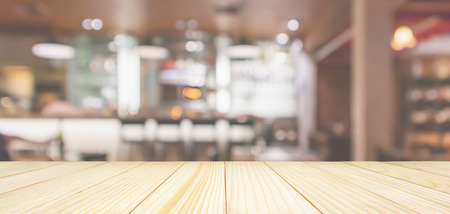 Photo pour Wood table top with Cafe Restaurant interior with bar counter blur abstract background with bokeh light - image libre de droit