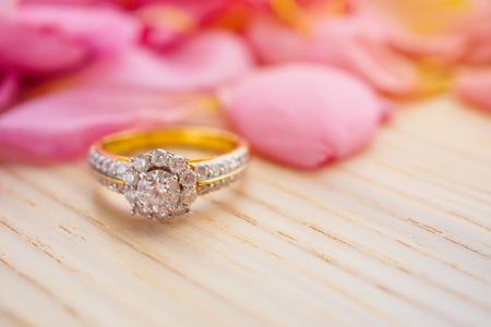 Foto de Jewelry diamond ring on wood table with beautiful pink rose petal background close up - Imagen libre de derechos