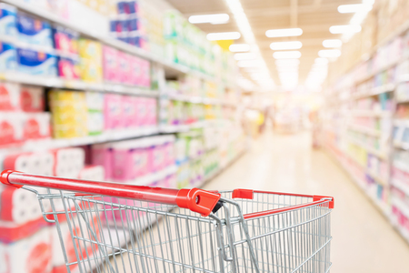 Foto de Empty shopping cart with abstract blur supermarket discount store aisle and toilet tissue paper display product shelves interior defocused background - Imagen libre de derechos