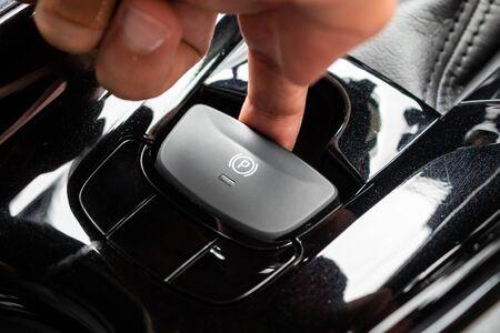 Photo pour Hand push on electronic handbrake button in luxury modern car - image libre de droit