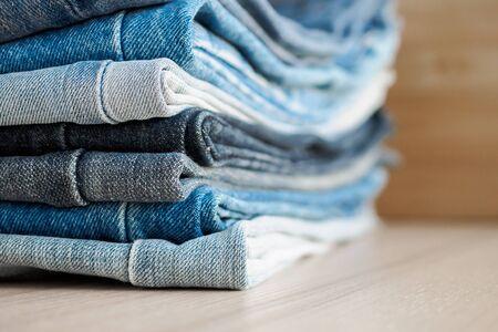 Photo pour denim blue jeans stack on wood table background - image libre de droit