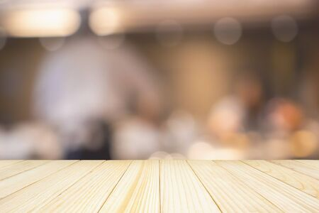 Photo pour Empty wood table top with Chef cooking in restaurant kitchen abstract blurred defocused background - image libre de droit