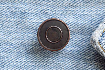 Photo pour Metal button on blue denim jeans background - image libre de droit