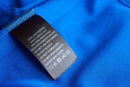 Photo pour Black laundry care washing instructions clothes label on blue jersey polyester sport shirt - image libre de droit
