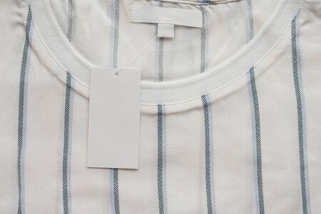 Foto de Blank white clothes tag label on new shirt - Imagen libre de derechos