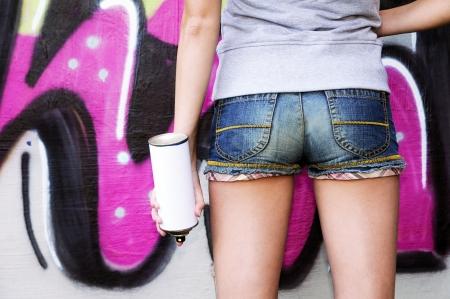 Girl holding spray against graffiti wall
