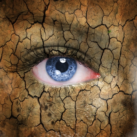 Cracked earth pattern on human face with blue eye.