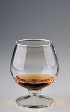 Single glass with brandy in it over gradient background.
