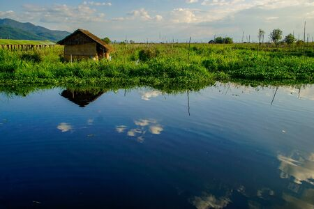 The calm, still waters of Inlay lake reflect the clouds and the blue sky, at Maing Thauk village in Inle Lake in Myanmar (Burma)の素材 [FY310141893846]