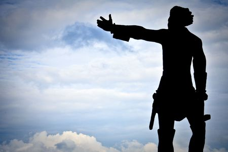 statue of the man with hist hand directed to the blue sky with clouds