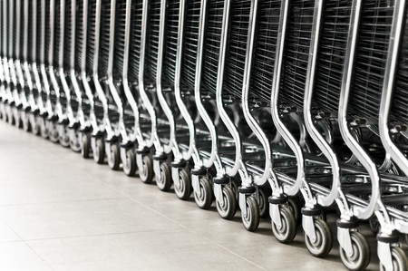 row of empty shopping carts in the big supermarket (extremely shallow depth of field, focus on fourth wheel from right)