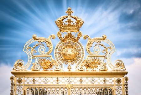 Golden ornate gate of Chateau de Versailles with blue sky, with clouds background. Rays of light from gate. Paris, France, Europe.